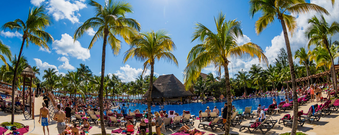 Our host resort - the Barcelo Maya pool with people sitting in pool chairs