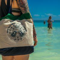 Dave & Tim canvas merch tote bag at the beach