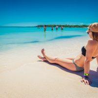 Girl in bikini on white sand beach with crystal ocean