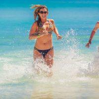 Girls in bikinis splashing in ocean water