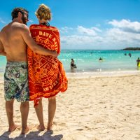 Couple enjoys the beach in official Dave and Tim towel