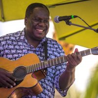 Vusi Mahlasela playing guitar
