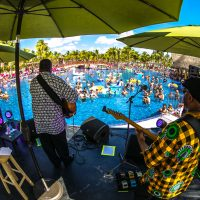 Vusi Mahlasela playing guitar by the pool