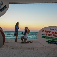 Man proposes to woman with photobooth frame & ocean