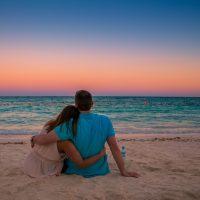 Man & woman watch sunset on white sand beach in Caribbean